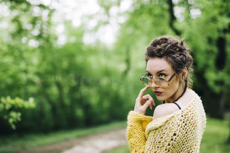 Portret van vrij jonge vrouw met glazen in het park stock afbeelding