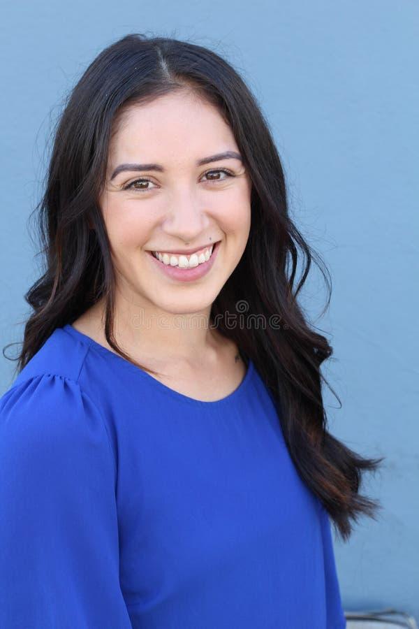 Portret van vrij Jonge Vrouw Status door Blauwe Muur royalty-vrije stock afbeelding