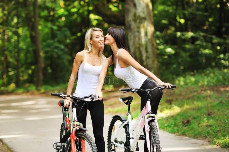 Portret van vrij jonge vrouwen met fiets in een park royalty-vrije stock afbeelding