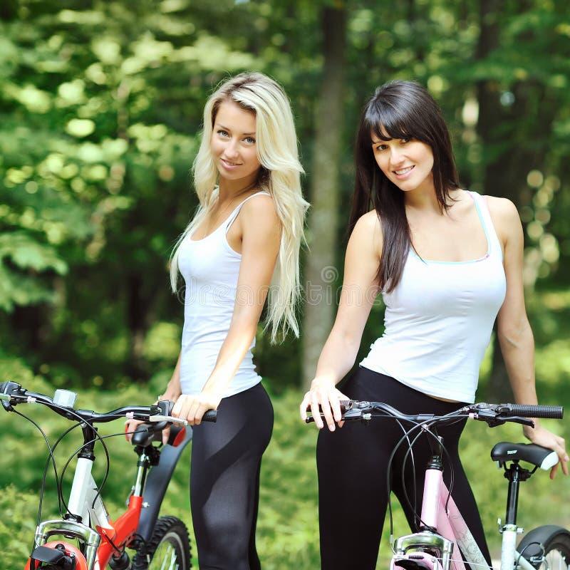 Portret van vrij jonge vrouwen met fiets in een park die glimlachen - royalty-vrije stock foto