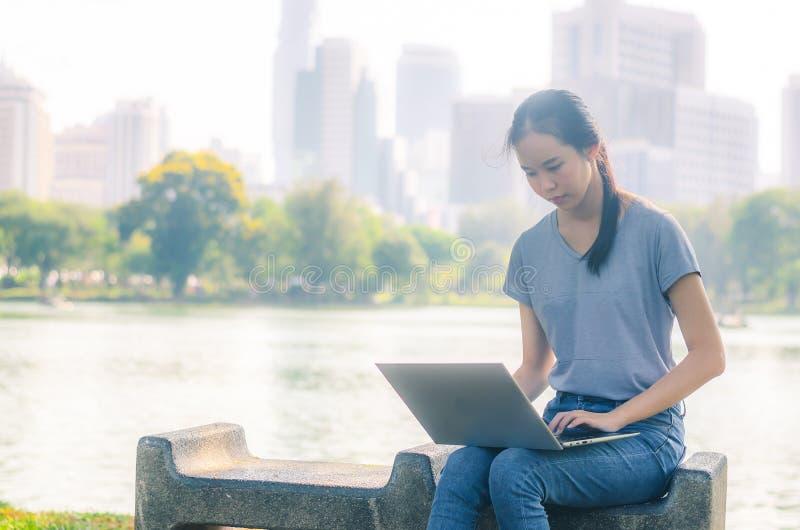 Portret van vrij jonge vrouwenzitting op bank in park tijdens de zomerdag terwijl het gebruiken van laptop van online het winkele royalty-vrije stock afbeeldingen