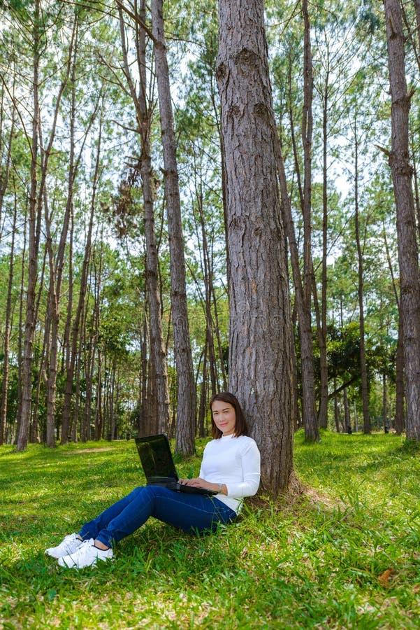 Portret van vrij jonge vrouwenzitting op groen gras in de dag van de parkzomer terwijl het gebruiken van laptop stock afbeeldingen