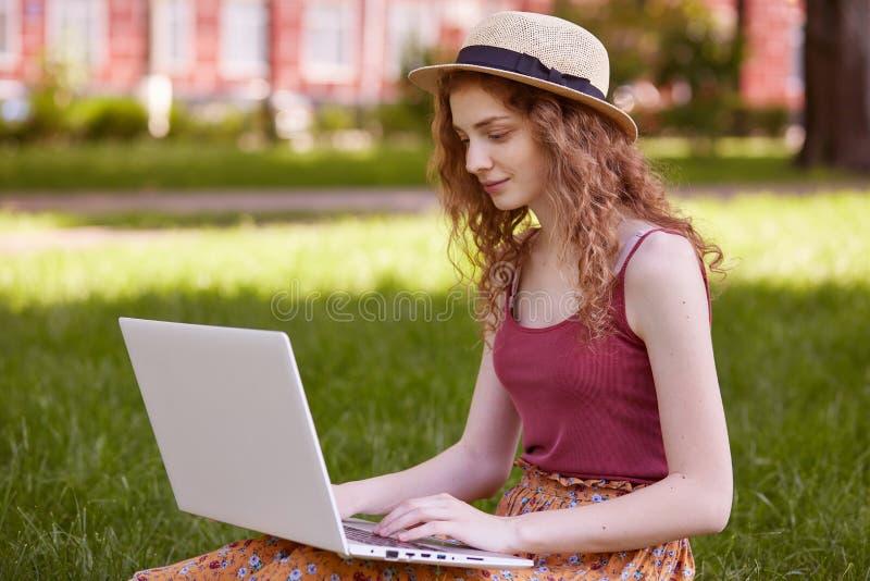 Portret van vrij jonge vrouwenzitting op groen gras in park met laptop op benen, het besteden de zomerdag werken openlucht, het g royalty-vrije stock foto's