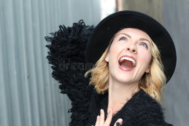 Portret van vrij vrolijke vrouw die zwarte bontkleding en moderne hoed in koude weerdag dragen Het lopen in openlucht in de winte royalty-vrije stock afbeeldingen