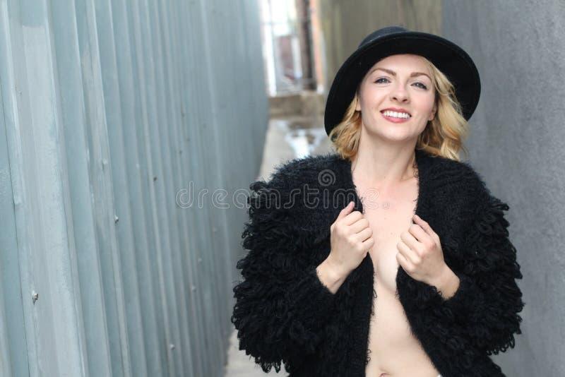 Portret van vrij vrolijke vrouw die zwarte bontkleding en moderne hoed in koude weerdag dragen Het lopen in openlucht in de winte royalty-vrije stock afbeelding