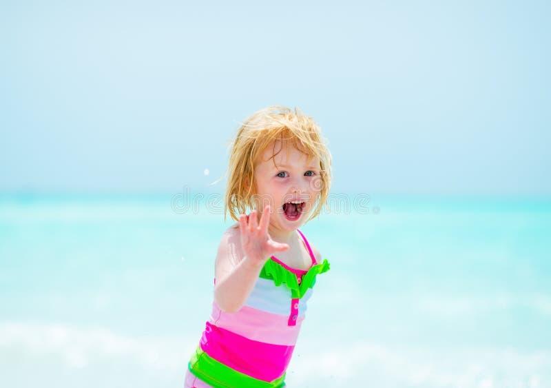 Portret van vrolijk babymeisje op strand stock afbeelding
