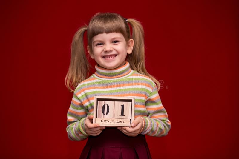Portret van vrolijk die meisje op rode greep houten die kalender wordt geïsoleerd op fir wordt geplaatst september royalty-vrije stock fotografie