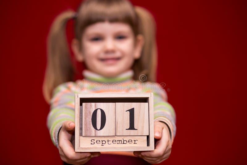 Portret van vrolijk die meisje op rode greep houten die kalender wordt geïsoleerd op fir wordt geplaatst september stock foto's