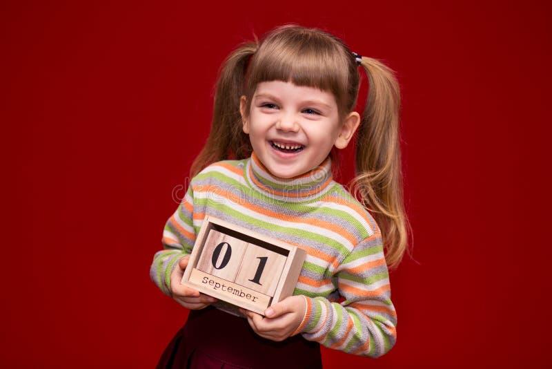 Portret van vrolijk die meisje op rode greep houten die kalender wordt geïsoleerd op fir wordt geplaatst september royalty-vrije stock afbeeldingen