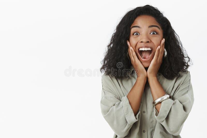 Portret van vrolijk enthousiast en opgetogen verrast donker-gevild meisje die met krullend kapsel schreeuwen van royalty-vrije stock fotografie