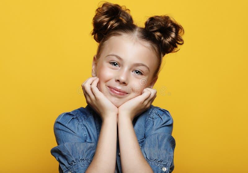 Portret van vrolijk glimlachend meisje op gele achtergrond stock foto's