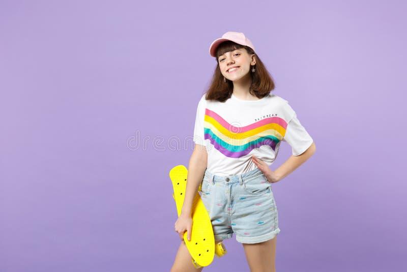 Portret van vrolijk glimlachend tienermeisje die in levendige kleren geel die skateboard houden op violette pastelkleurmuur wordt stock afbeelding