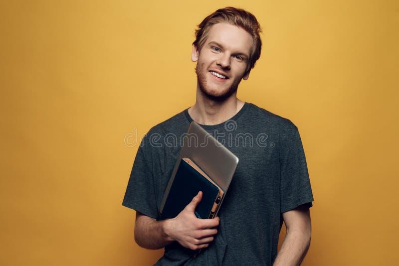Portret van Vrolijk Jong Guy Holding Laptop stock afbeeldingen