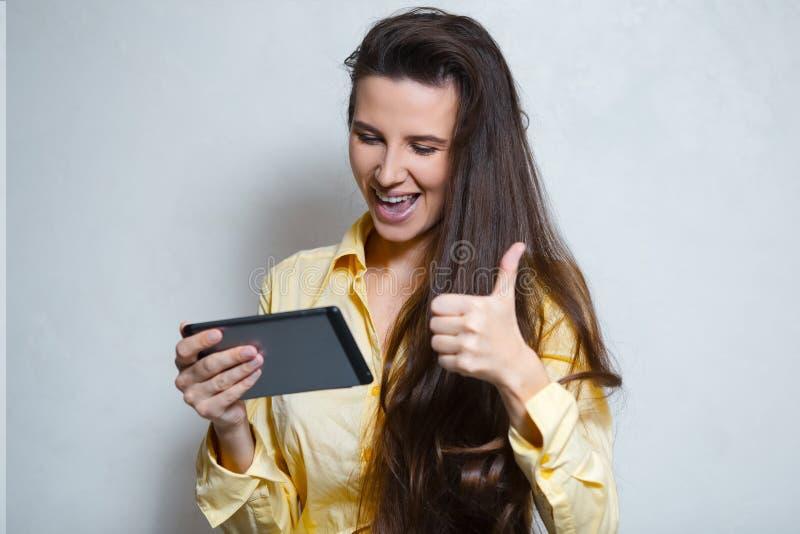 Portret van vrolijk jong meisje die duim met in hand smartphone tonen Gekleed in geel overhemd royalty-vrije stock foto's