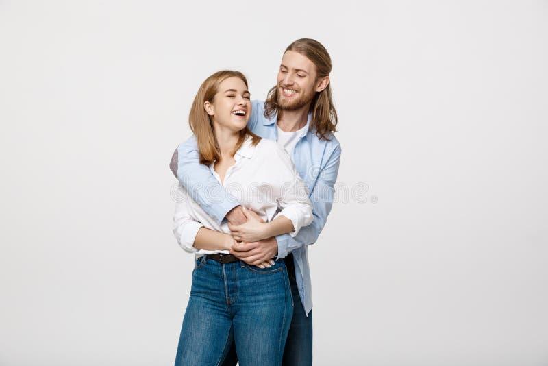Portret van vrolijk jong paar die en elkaar op geïsoleerde witte achtergrond bevinden zich koesteren stock foto's