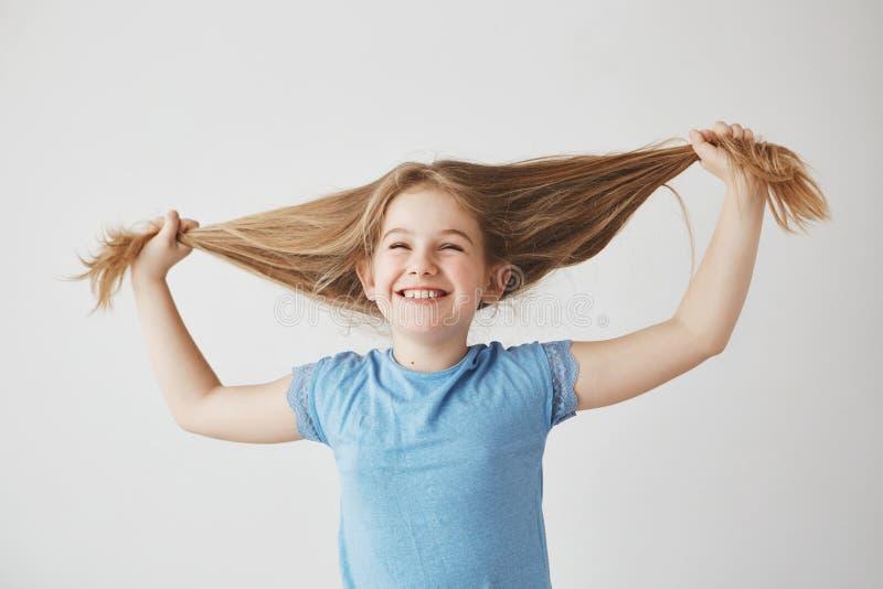 Portret van vrolijk leuk weinig blond meisje die in blauwe t-shirt met gesloten ogen lachen, houdend haar met handen, die hebben royalty-vrije stock foto's
