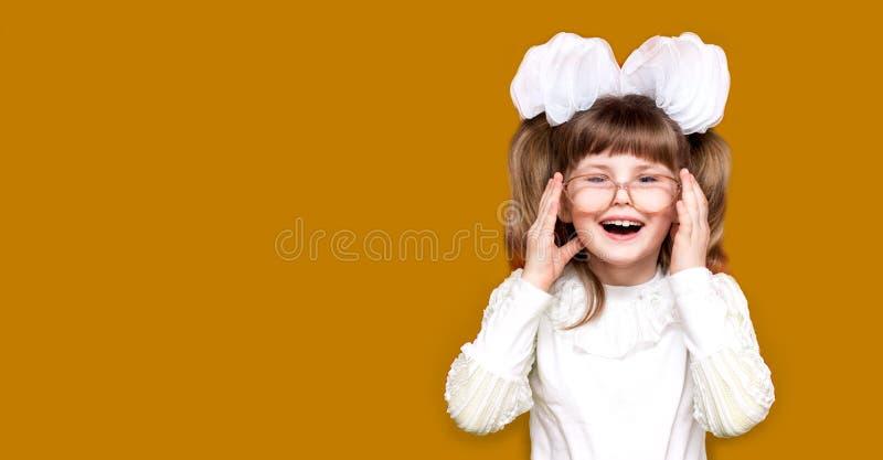 Portret van vrolijk meisje in zeer grote die glazen op geel wordt geïsoleerd Concept zicht of het onderwijs stock afbeeldingen