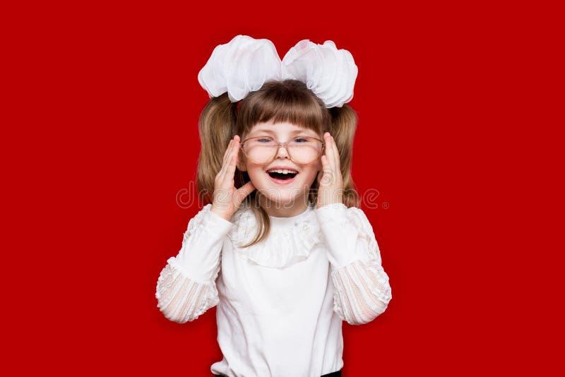 Portret van vrolijk meisje in zeer grote die glazen op rood wordt geïsoleerd Concept zicht of het onderwijs royalty-vrije stock foto