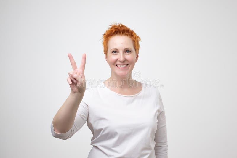 Portret van vrolijk mooi rijp womanwith kort rood kapsel die twee vingers of overwinningsgebaar tonen royalty-vrije stock foto's