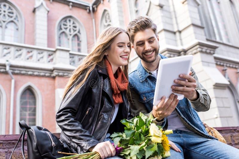 portret van vrolijk paar die digitale tablet gebruiken samen terwijl het rusten royalty-vrije stock afbeelding