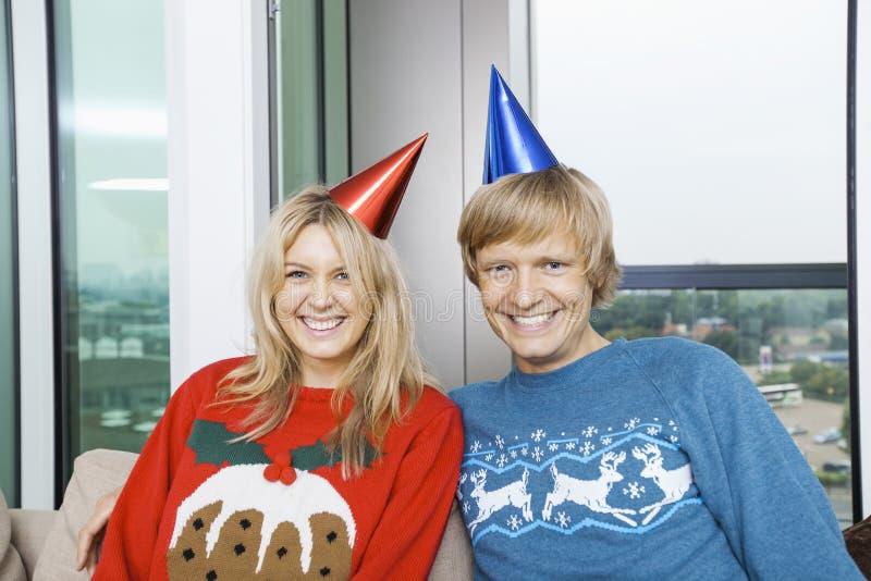 Portret van vrolijk paar dat Kerstmissweaters en partijhoeden in woonkamer thuis draagt royalty-vrije stock foto's
