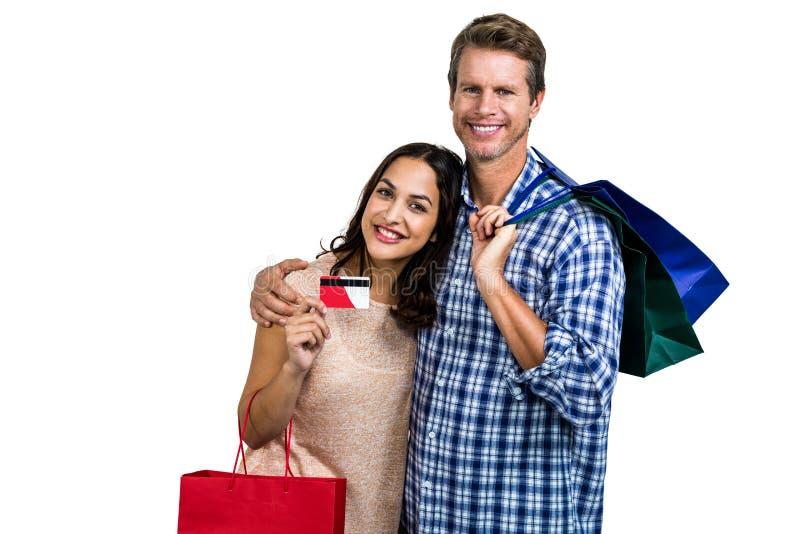 Portret van vrolijk paar met het winkelen zakken en creditcard royalty-vrije stock foto's