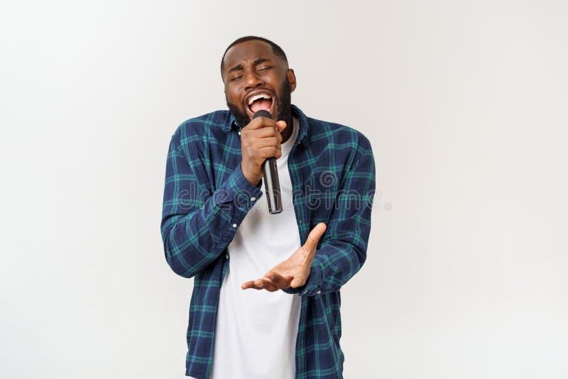 Portret van vrolijk positief elegant knap Afrikaans de microfoon van de mensenholding het zingen lied Ge?soleerdj op witte achter stock afbeeldingen