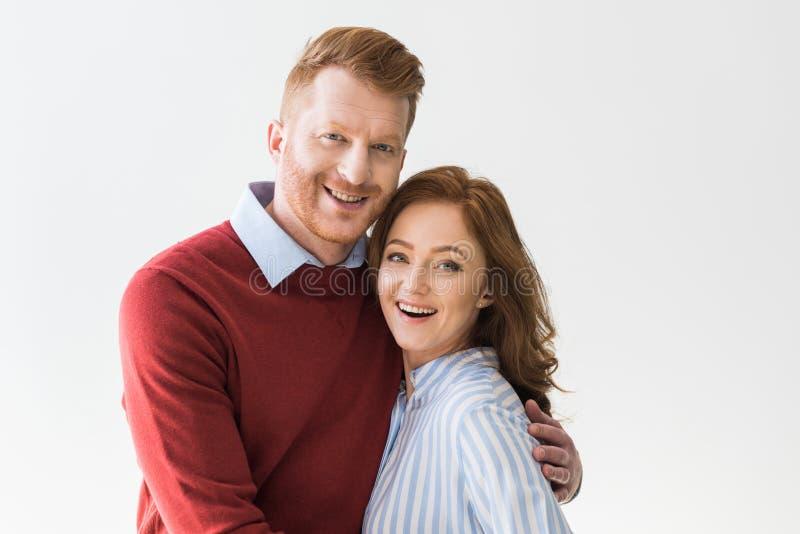 portret van vrolijk roodharigepaar die zich en bij camera glimlachen verenigen stock foto's