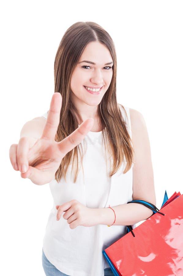 Portret van vrolijk succesvol meisje die overwinningsteken doen en smil stock afbeeldingen