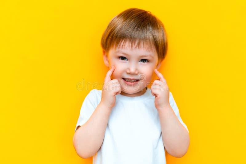 Portret van vrolijk weinig oud jongenskind drie jaar, status geïsoleerd over gele achtergrond kijkend camera het tonen van wit royalty-vrije stock afbeeldingen