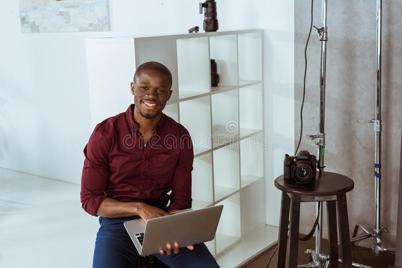 portret van vrolijke Afrikaanse Amerikaanse fotograaf die met laptop camera bekijken royalty-vrije stock fotografie
