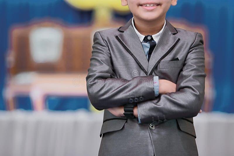 Portret van vrolijke Aziatische jongen met slimme kleren die gekruiste wapens bevinden zich stock fotografie