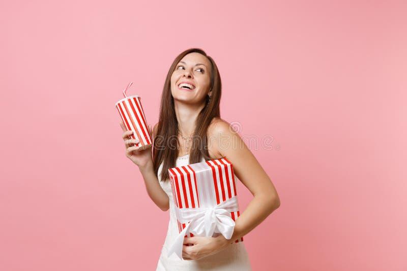 Portret van vrolijke bruidvrouw die in huwelijkskleding omhoog greep rode doos met gift, huidige, plactic kop met kola kijken of royalty-vrije stock afbeeldingen