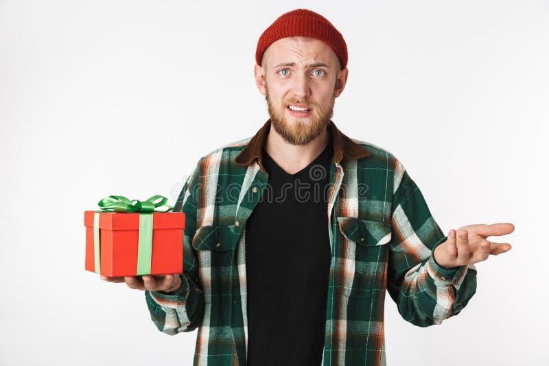 Portret van vrolijke gebaarde kerel die hoed en plaidoverhemd dragen die huidige doos houden, terwijl status geïsoleerd over witt royalty-vrije stock foto