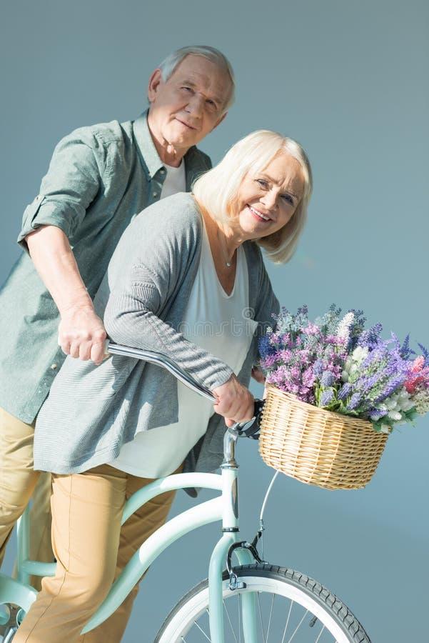 Portret van vrolijke hogere paar berijdende fiets samen royalty-vrije stock afbeeldingen