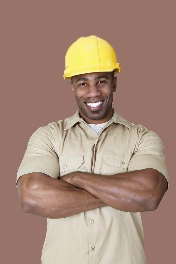 Portret van vrolijke jonge Afrikaanse bouwvakker over bruine achtergrond royalty-vrije stock afbeeldingen