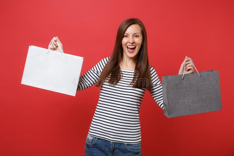 Portret van vrolijke jonge vrouw die in gestreepte kleren pakkettenzakken met aankopen na winkelen houden geïsoleerd op rood royalty-vrije stock foto