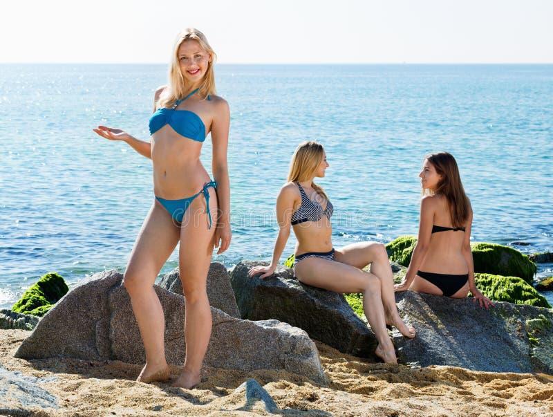 Portret van vrolijke jonge vrouw status op rotsachtig strand royalty-vrije stock afbeelding