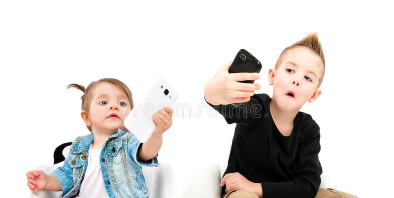Portret van vrolijke jongen en leuk meisje die selfie op mobiele telefoon nemen stock fotografie