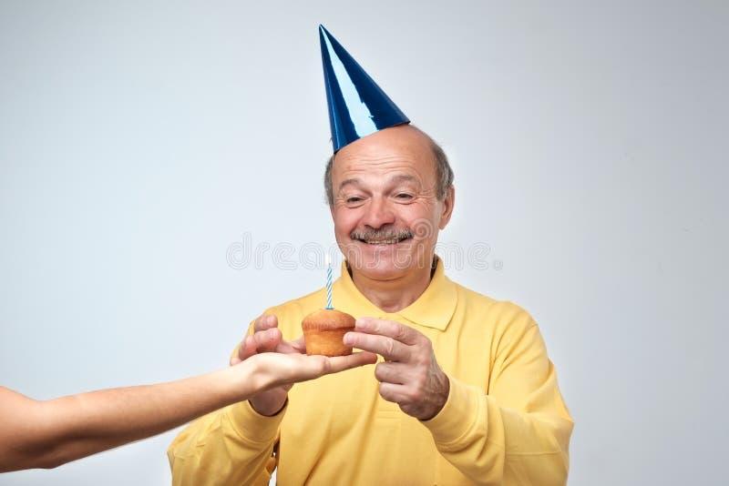 Portret van vrolijke knappe verjaardagskerel met in grappige cao Zijn vriend die hem verjaardag geven cupcake royalty-vrije stock afbeeldingen