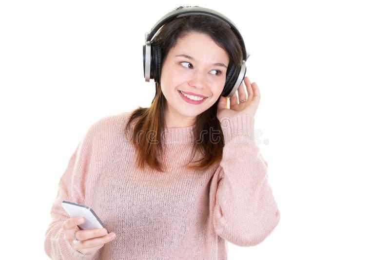 Portret van vrolijke leuke jonge die vrouw het luisteren muziek in hoofdtelefoons op witte achtergrond wordt geïsoleerd die telef royalty-vrije stock fotografie