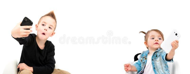 Portret van vrolijke leuke jonge geitjes die selfie op mobiele telefoon nemen stock afbeeldingen