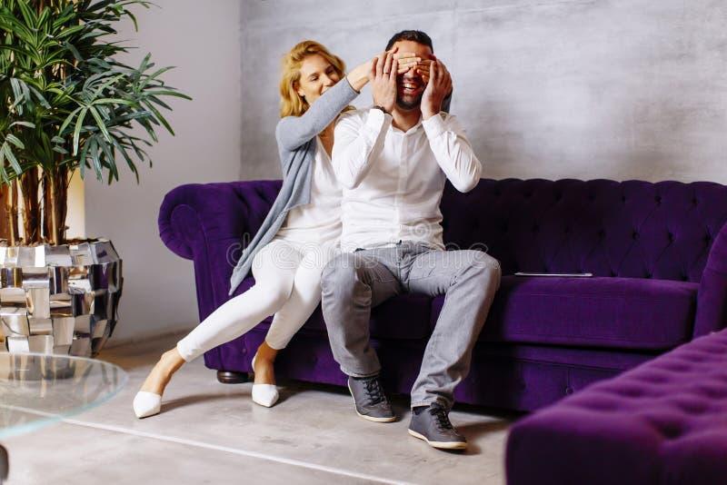 Portret van vrolijke paarzitting in bank thuis stock foto's