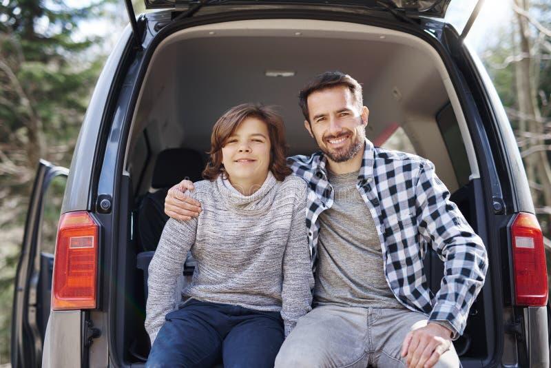Portret van vrolijke papa en zijn het tienerzoon omhelzen stock afbeelding