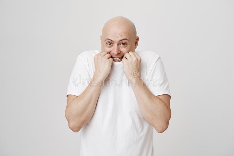 Portret van vrolijke positieve kale Kaukasische mannelijke trekkende t-shirt op gezicht alsof willend van camera verbergen, die g royalty-vrije stock afbeeldingen