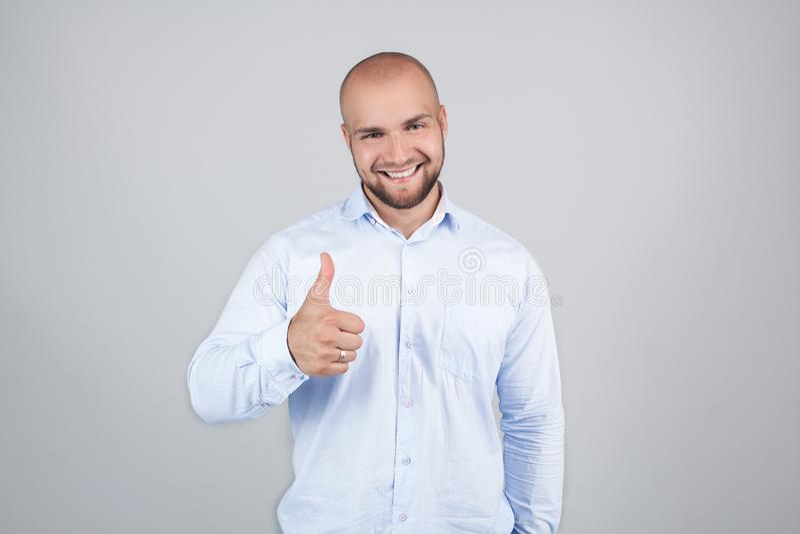 Portret van vrolijke verrukkelijke opgewekte blije knap met het richten van toothy glanzende glimlachmens die blauw modieus moder stock afbeelding