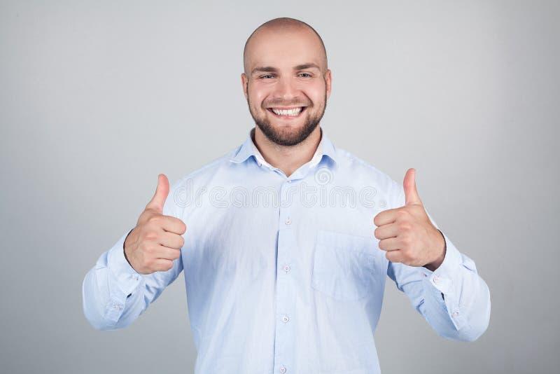 Portret van vrolijke verrukkelijke opgewekte blije knap met het richten van toothy glanzende glimlachmens die blauw modieus moder stock fotografie