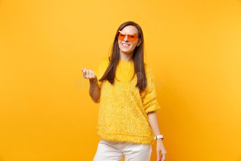 Portret van vrolijke vrij jonge vrouw in bontsweater, witte broek, hart oranje glazen status geïsoleerd op helder royalty-vrije stock afbeelding