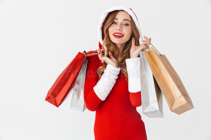 Portret van vrolijke vrouwenjaren '20 die het rode kostuum die van Santa Claus dragen en kleurrijke document het winkelen zakken  stock afbeelding