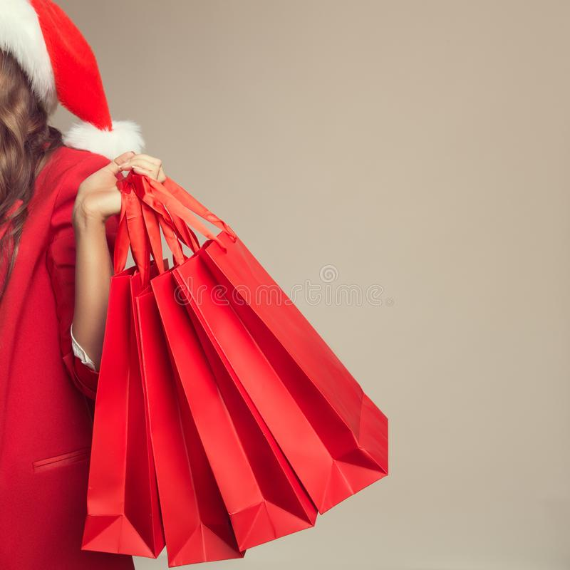 Portret van vrouw in de hoed van de Kerstman Het houden van rode het winkelen zakken stock fotografie